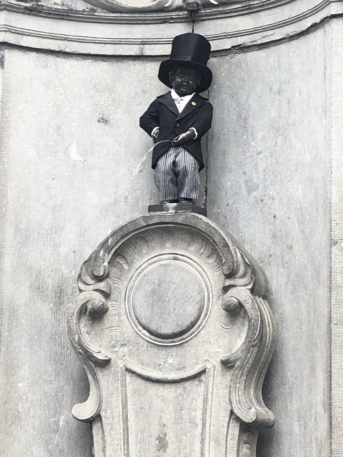 Manneken Pis dressed like a rich businessman or something.